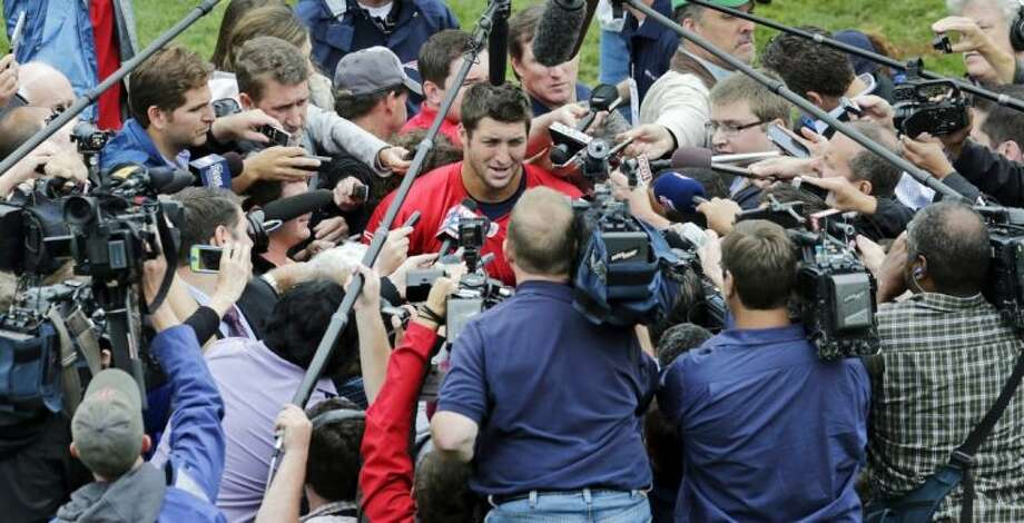 New England Patriots quarterback Tim Tebow is surrounded by reporters and cameramen after his first practice with the team. Photo: Charles Krupa