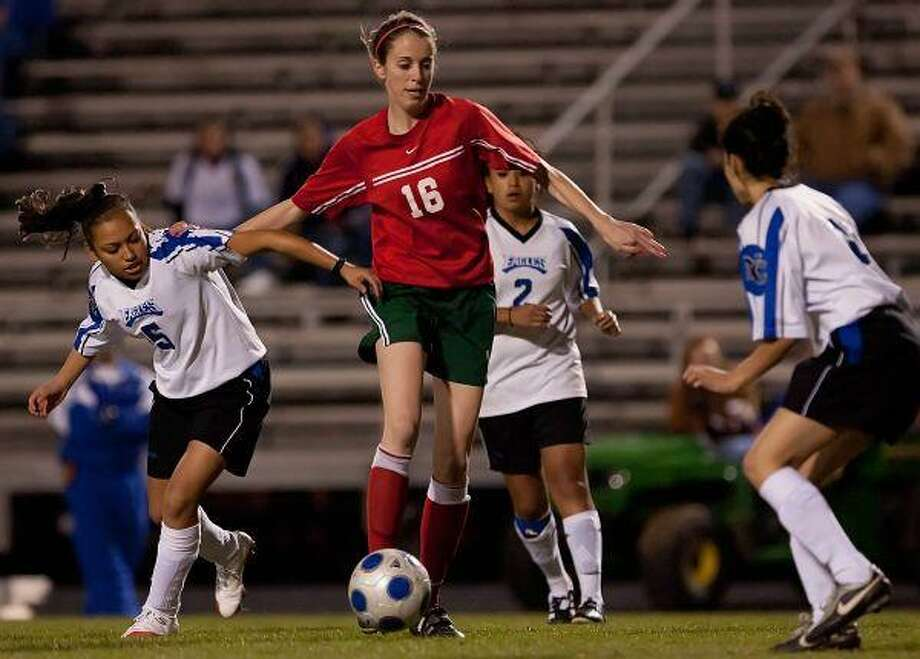 The Woodlands' Molly Missimer dribbles downfield against New Caney's Vicky Ramirez (5) and Leslie Sosa, right, during Friday night's game at Don Ford Stadium in New Caney. / The Courier