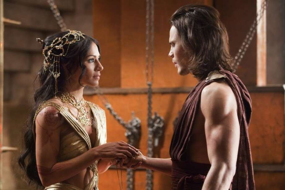 "In this film image released by Disney, Lynn Collins, of Houston, portrays Dejah Thoris, left, and Taylor Kitsch portrays John Carter in a scene from ""John Carter."""