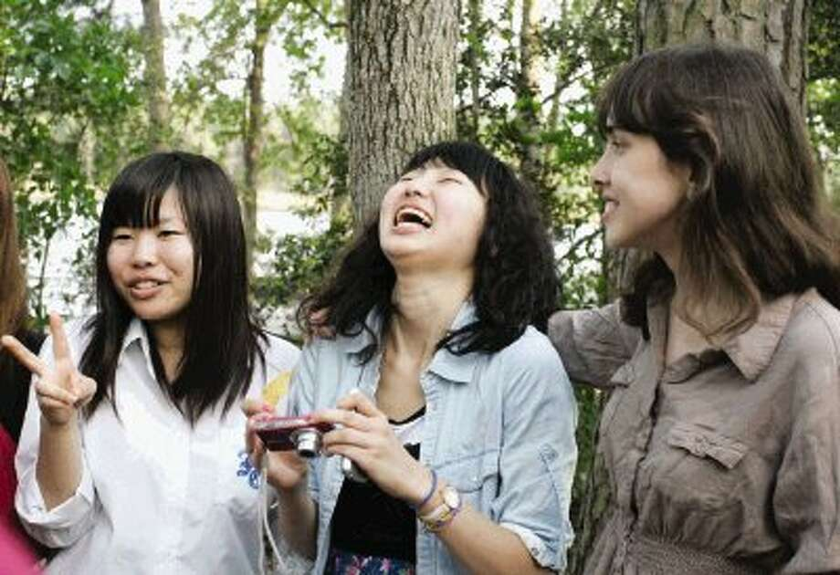 Visiting Japanese student Ikuko Akita, center, shares a laugh with College Park High School student Maya Cantor, right, as the pair posed for photographs at a farewell party Friday at Northshore Park in The Woodlands. Pictured at left is Rinka Kuroiwa, showing a peace sign. / The Courier