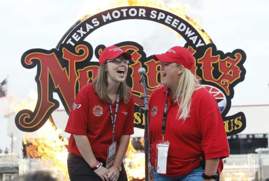 "Jennifer Simonds, left, and Anna ""Sam"" Canaday, teachers from Plaza Towers Elementary School in Moore, Okla., give the command to start engines for the IndyCar auto race Saturday in Fort Worth. The teachers are from the school that was hit by a tornado May 20 and both used their bodies to shield kindergartners when their school took a direct hit. Photo: Tim Sharp"