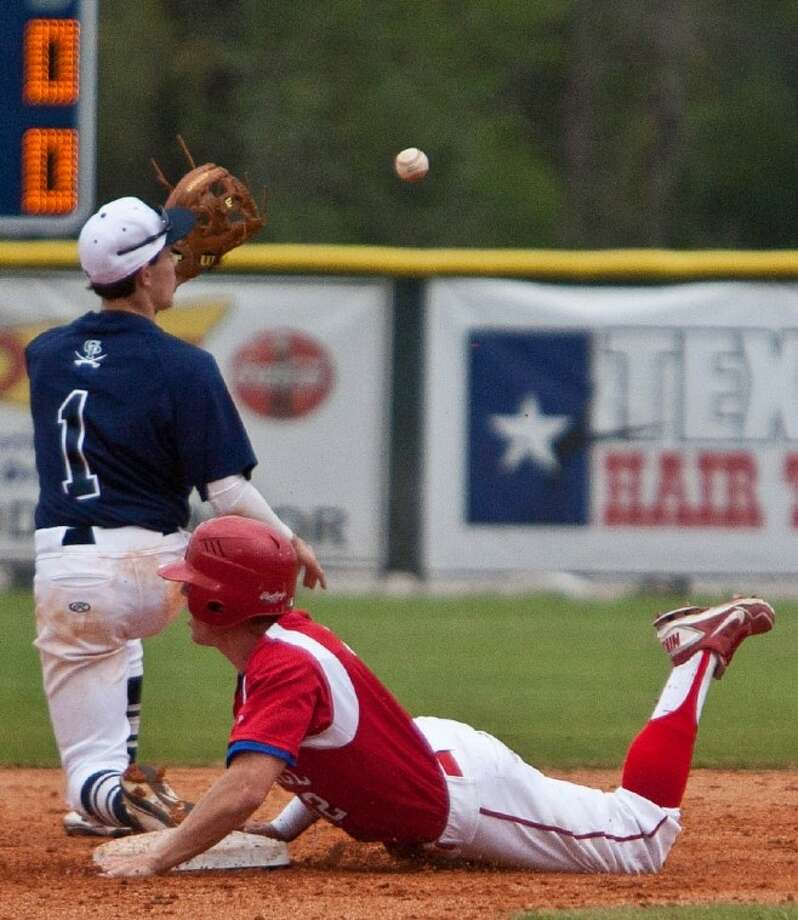 College Park's Dakota Parsons reels in a relay throw as Tomball's Troy Gillen slides safely into second base during Thursday's game.