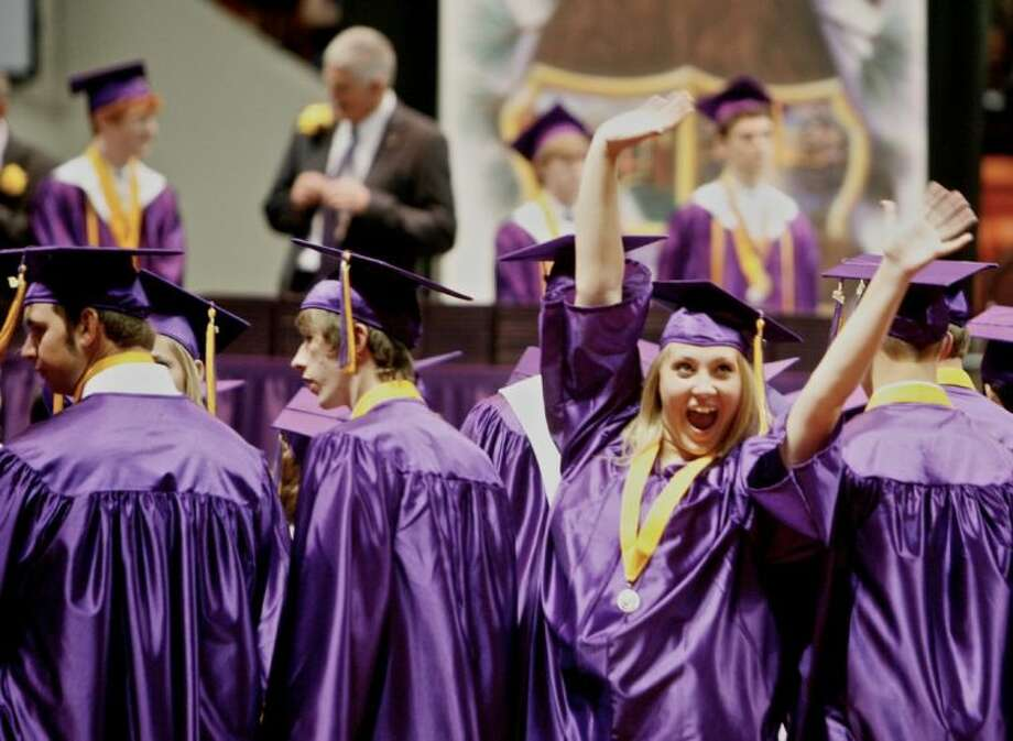 A Montgomery High School graduate excitedly waves to family members after entering Johnson Coliseum during Saturday's ceremony in Huntsville. To view or order this photo and others like it, visit: HCNPics.com Photo: Staff Photo By Eric Swist