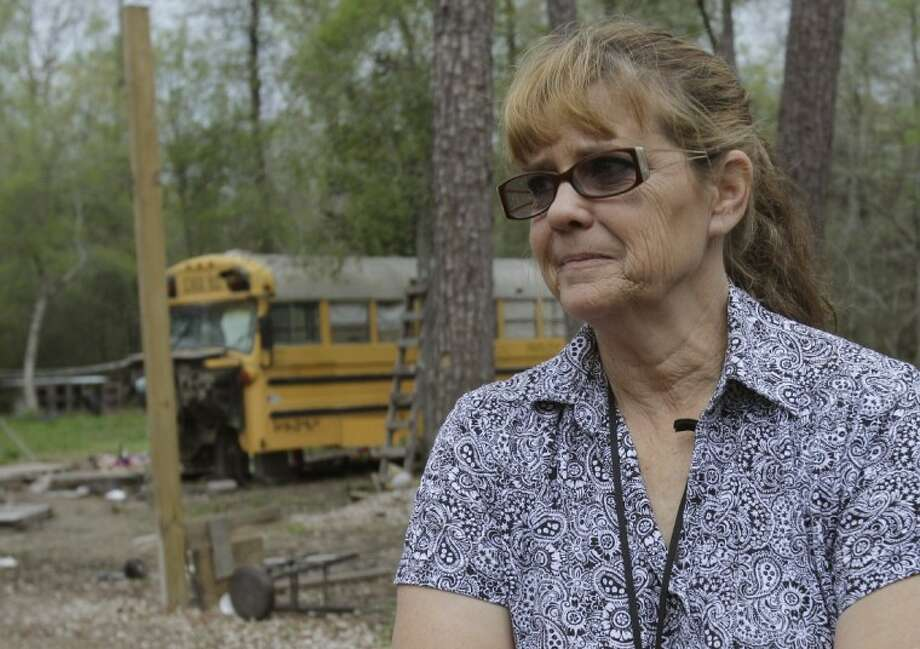 Postal carrier Vanessa Picazo stands outside the converted school bus Thursday in Splendora where she discovered two young children living. The children, ages 11 and 5, are now in the custody of child welfare authorities. Photo: AP Photo