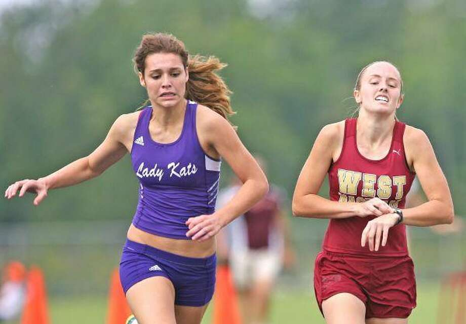 Willis freshman Cali Roper edges out in front of Magnolia West's Rachel Melton to win the 1600-meter run during Thursday's District 18-4A track and field meet hosted by Magnolia High School. Roper and Melton will be advancing to the regional meet in Huntsville. / The Courier