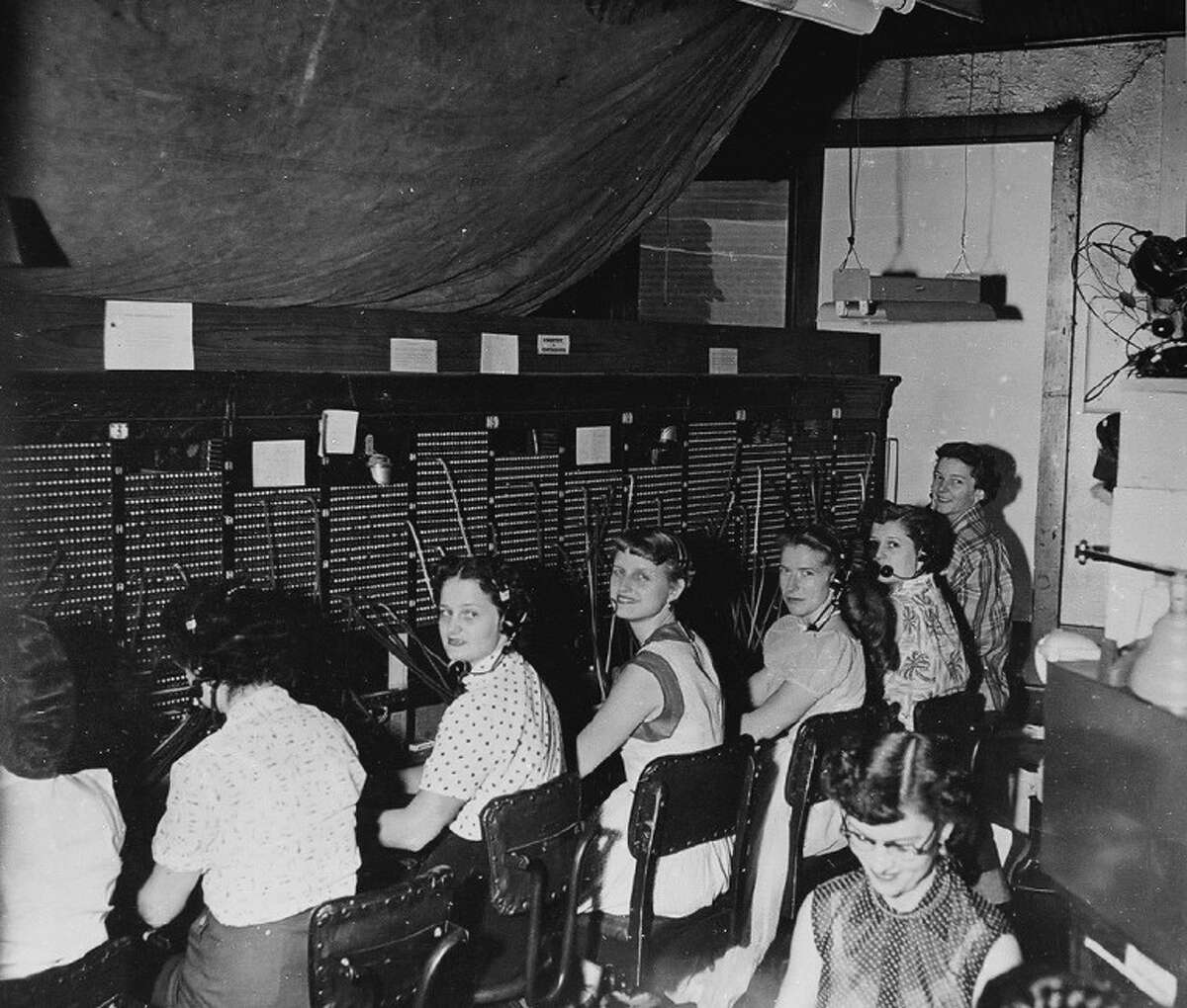 """The Conroe Telephone Company was in the second floor of the Madeley Building. Here lady operators work the switchboard. According to Vera Acrey, who was a switchboard operator, the ladies would ask """"number please"""" and the caller would respond with a three-digit number."""