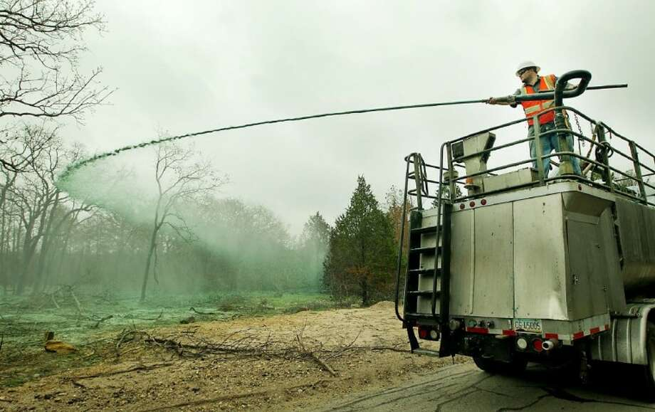 Supervisor Chris Becher operates a hose that sprays seed mixture from a slow-moving truck in Bastrop State Park. Restoring pines lost in Bastrop fires will take years, millions of dollars, and plenty of help, officials say. Photo: Ralph Barrera