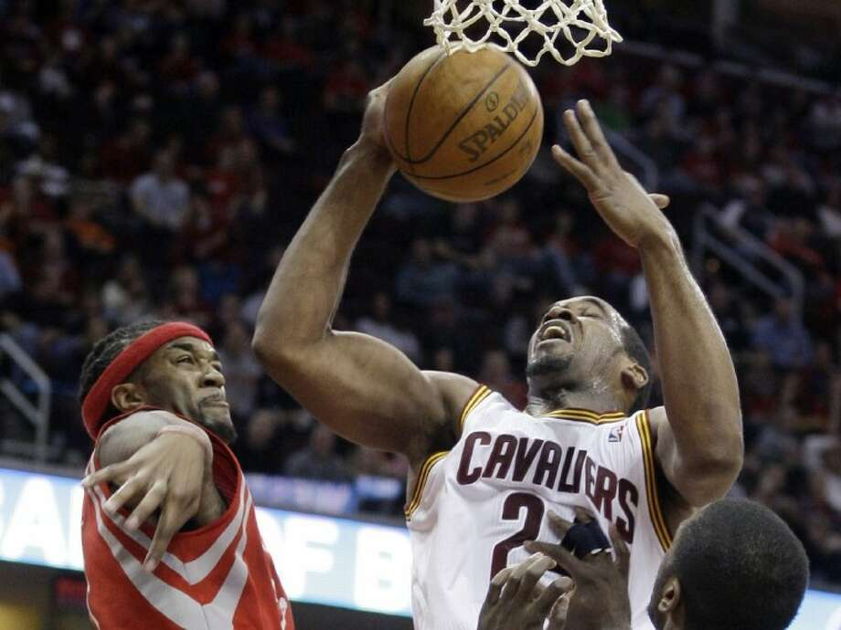 Houston Rockets' Jordan Hill, left, knocks the ball loose from Cleveland Cavaliers' Samardo Samuels in the second quarter Sunday in Cleveland. Photo: Tony Dejak
