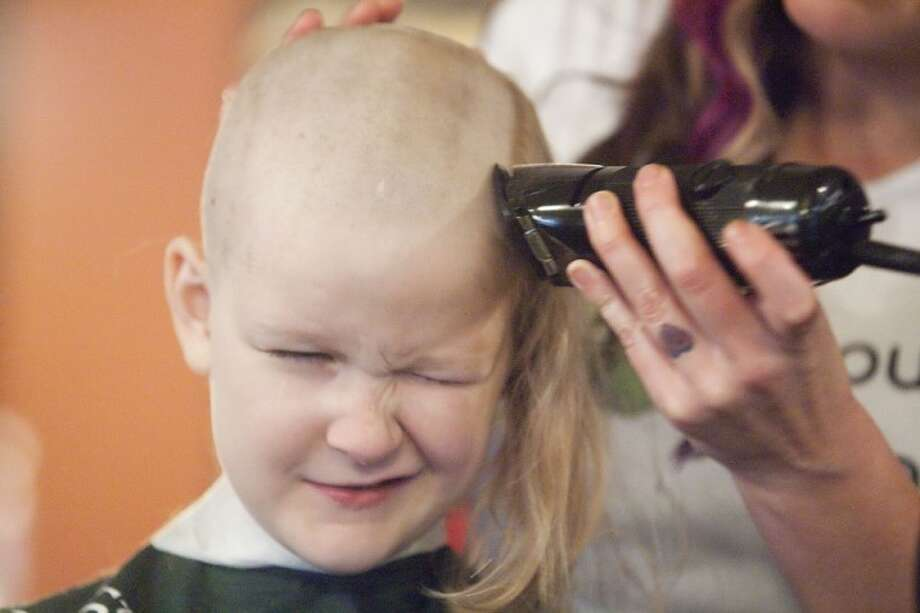 Bailey Hayes, 9, has her head shaved by Jenny Bussolati during a fundraiser for the St. Baldrick's Foundation Sunday at the Goose's Acre in The Woodlands. Photo: Karl Anderson