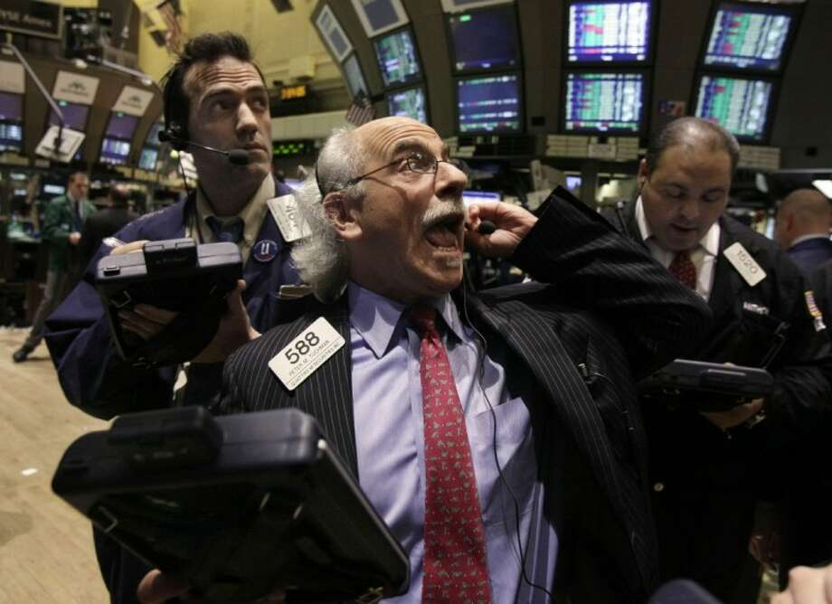 Trader Peter Tuchman, center, works on the floor of the New York Stock Exchange Tuesday. The Dow Jones industrial average rose 218 points and closed at its highest level since the end of 2007. Photo: Richard Drew