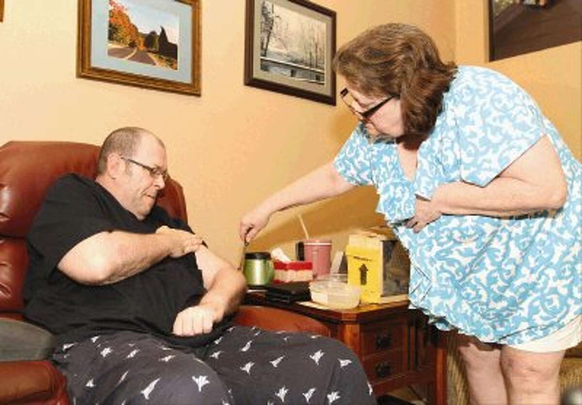Caretaker and sister Brenda Vozzo stings Alan Swor with bees at his home in The Woodlands. Swor, who has multiple sclerosis, receives 30 bee stings on his body every three days as part of his bee sting therapy to help relieve inflammation.