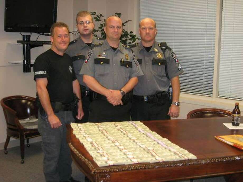 "Precinct 4 Lt. Mark Seals, Deputy Josh Bergland, Constable Kenneth ""Rowdy"" Hayden and Sgt. Ricky Warwick, left to right, check out approximately $270,000 in currency taken from the safety deposit box belonging to a New Caney man the officers arrested Wednesday."