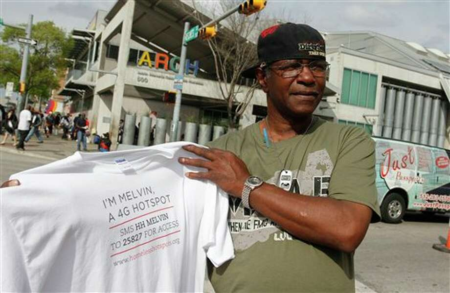 Melvin Hughes, a homeless man hired by BBH Labs to provide and promote a mobile 4G Wi-i service during SXSW, holds the T-shirt he was given by the marketing agency in Austin, Texas on Tuesday, March 13, 2012. (AP Photo/Jack Plunkett) Photo: AP Photo By Jack Plunkett / FR59553 AP
