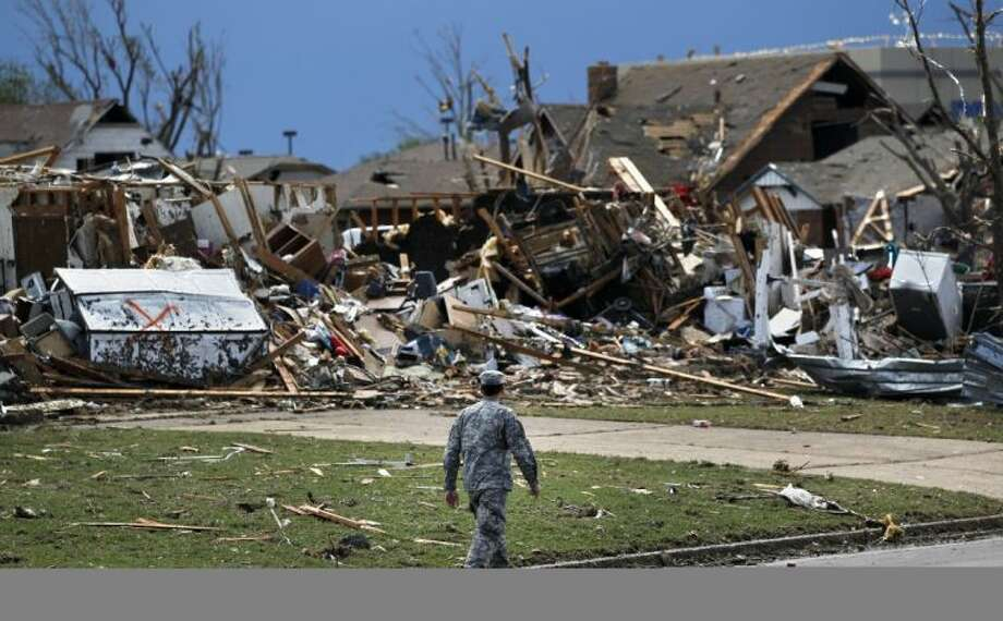 A soldier walks past the wreckage left when a tornado moved through Moore, Okla., Tuesday. Photo: Brennan Linsley