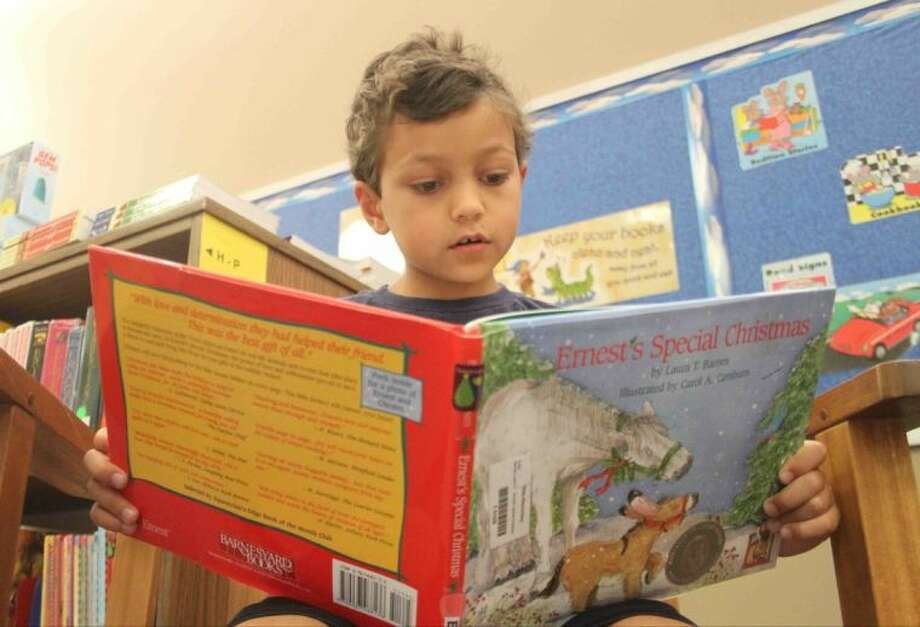 "First-grader Marco Warma reads ""Ernest's Special Christmas"" by Laura Barnes at Sally Ride Elementary. The school challenged its students to read 30,000 books. Photo: Staff Photo By Jason Fochtman"