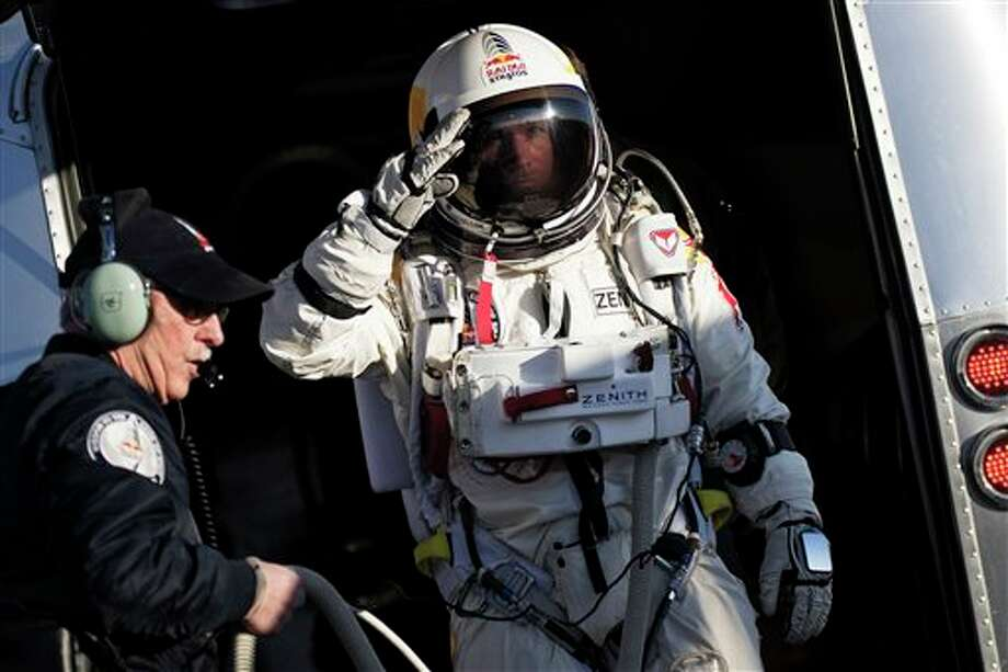 In this photo provided by Red Bull Stratos, Felix Baumgartner salutes as he prepares to board the capsule carried by a balloon during the first manned test flight for Red Bull Stratos in Roswell, N.M. on Thursday, March 15, 2012. Baumgartner is more than halfway toward his goal of setting a world record for the highest jump. A spokesperson says the skydiver took a practice jump from more than 13 miles high over New Mexico. He's aiming for nearly 23 miles in the summer. The record is held by Joe Kittinger who jumped from 19.5 miles in 1960. (AP Photo/Red Bull Stratos, Joerg Mitter) Photo: Ap Photo By Joerg Mitter / Free image for editorial usage only: Photo by Joerg Mitter for Red Bull Stratos Newsroom. NO ARCHIVE. NO SALES. FOR EDITORIAL USE ONLY. NOT FOR SALE FOR MARKETING OR ADVERTISING CAMPAIGNS. For more pictures, videos and TV material go to www.redbullstratosnewsroom.com. info +43664 3805053