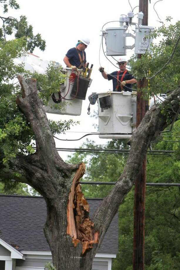 Workers for Entergy Texas repair a transformer in Conroe Wednesday morning. At its peak, Entergy Texas reported 1,800 outages from the storms that raced across the area.