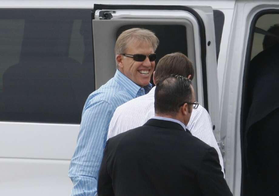 Denver Broncos executive John Elway, rear, smiles as he arrives at the Raleigh-Durham International Airport, Friday in Raleigh, N.C. Elway and coach John Fox traveled to North Carolina to watch Peyton Manning work out at Duke. Photo: Shawn Rocco