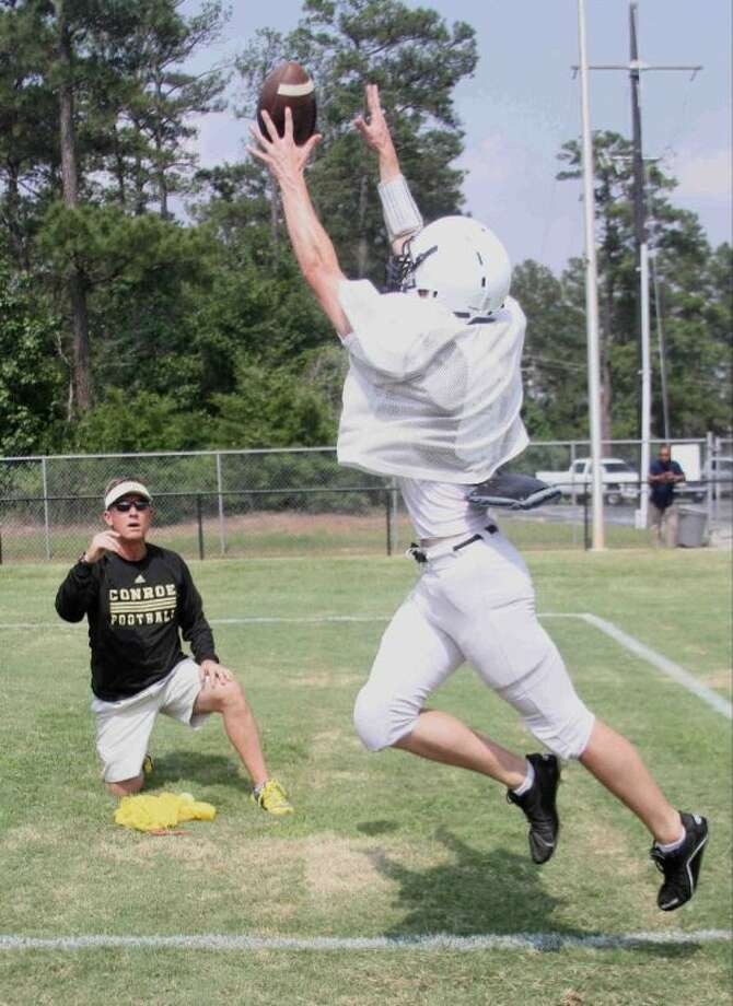 Conroe coach Robert Walker tosses a ball for a player during warm ups before the Tigers' spring football game on Thursday. To view or purchase this photo and others like it, visit HCNpics.com. Photo: Staff Photo By Jason Fochtman
