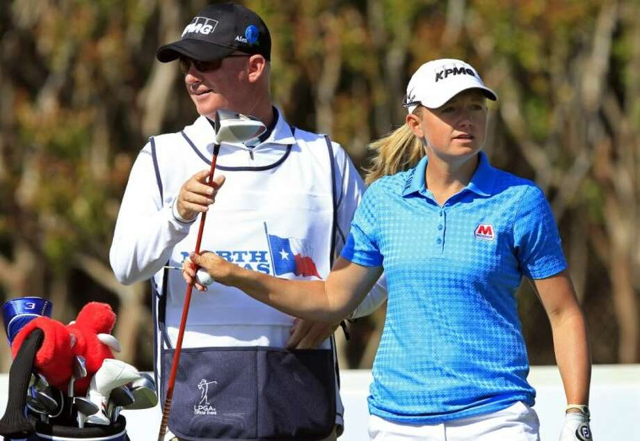 Caddie Travis Wilson hands Stacy Lewis a driver before she tees off on the 18th hole during the first round of the North Texas LPGA Shootout on Thursday at Los Colinas Country Club in Irving. Photo: John F. Rhodes