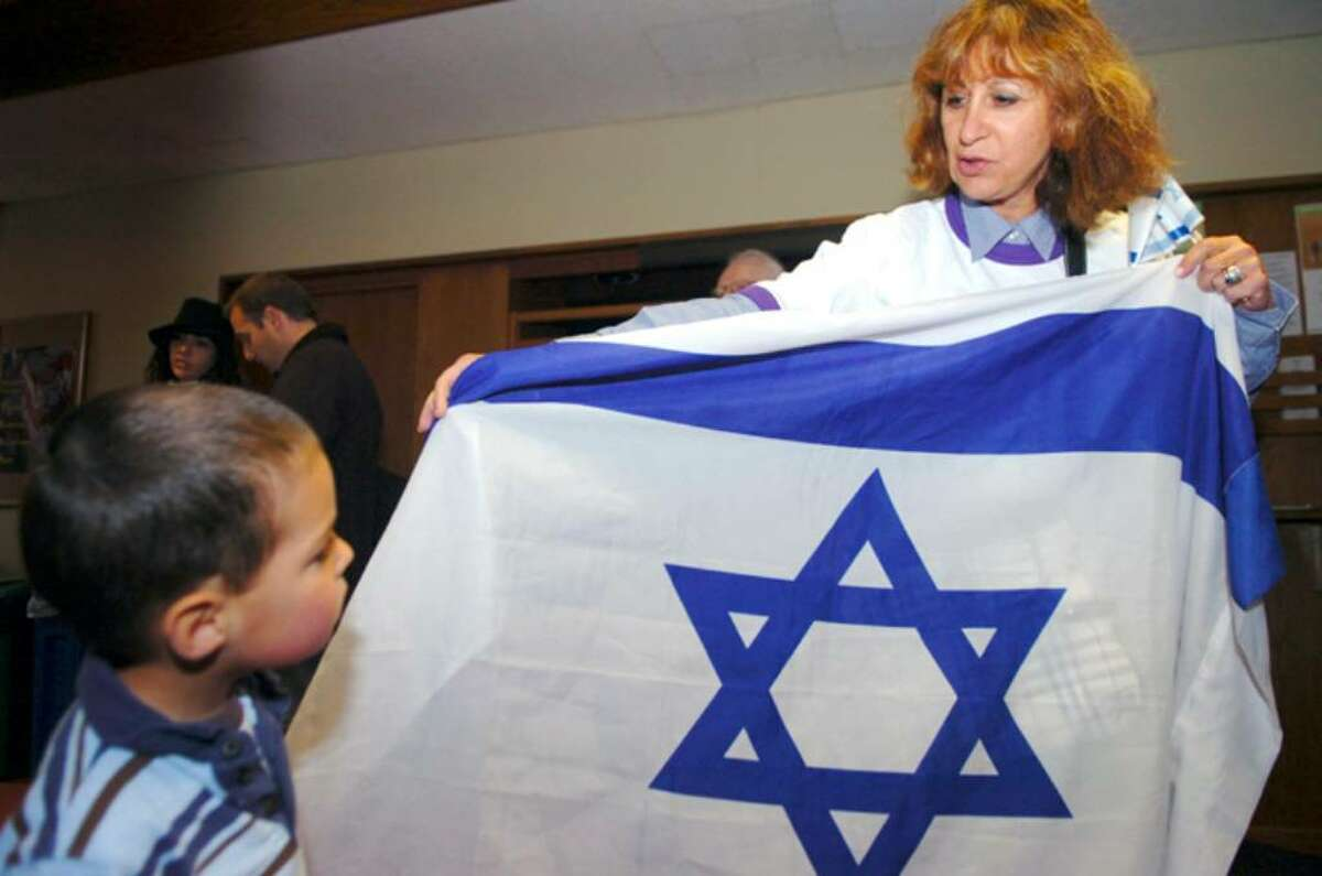 Ora Navok, left, a fifth and sixth grade teacher at the Temple Shalom holds out the Israel flag for Gilad Wiegenfeld, 3, to see at the celebration of Israel's 62 years, at Greenwich Town Hall on Sunday, April 25, 2010.