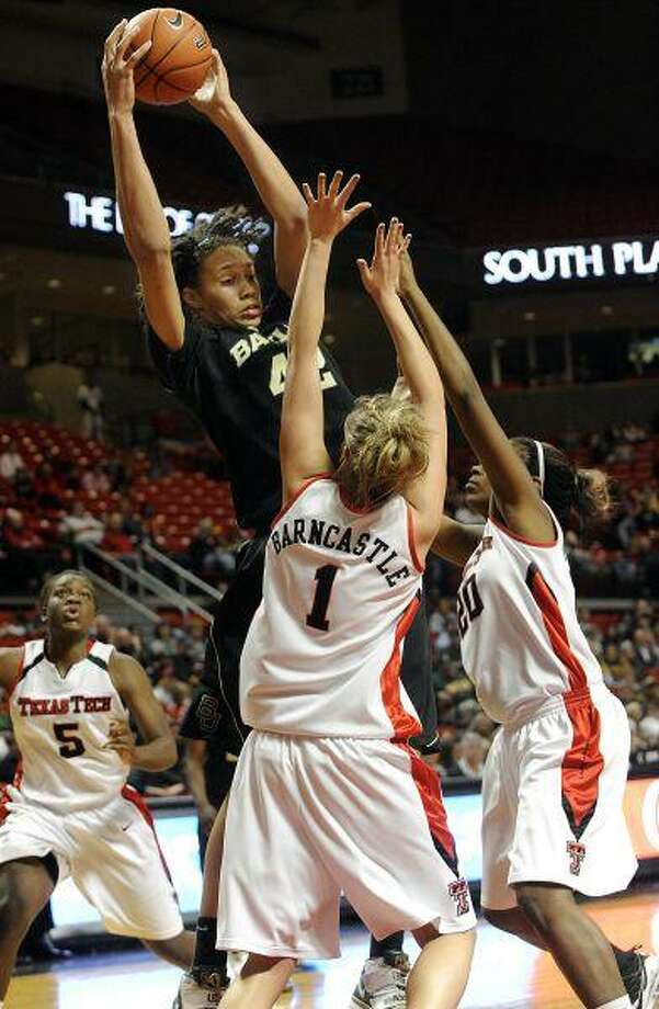 Baylor's Brittney Griner pulls in a rebound against Texas Tech's Jordan Barncastle and Kierra Mallard during the first half Wednesday in Lubbock. Griner was ejected from the game in the second half for punching Barncastle in the face. Baylor beat Texas Tech 69-60. / AP2010