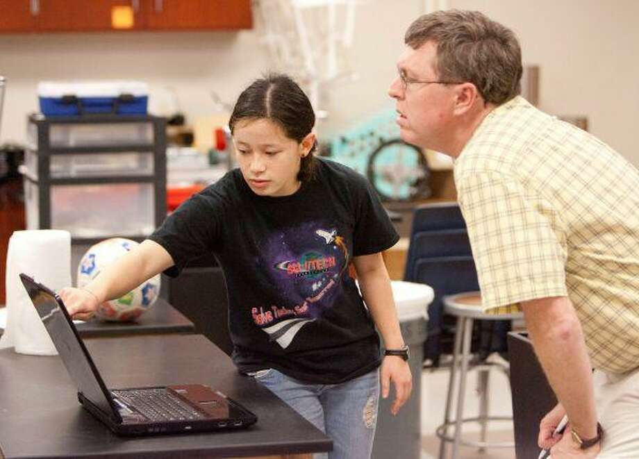 Academy of Science and Technology sophomore Stephanie Mallard shows teacher Scott Rippetoe her presentation in preparation for the Boosting Engineering, Science and Technology National Championship April 24th. / The Courier