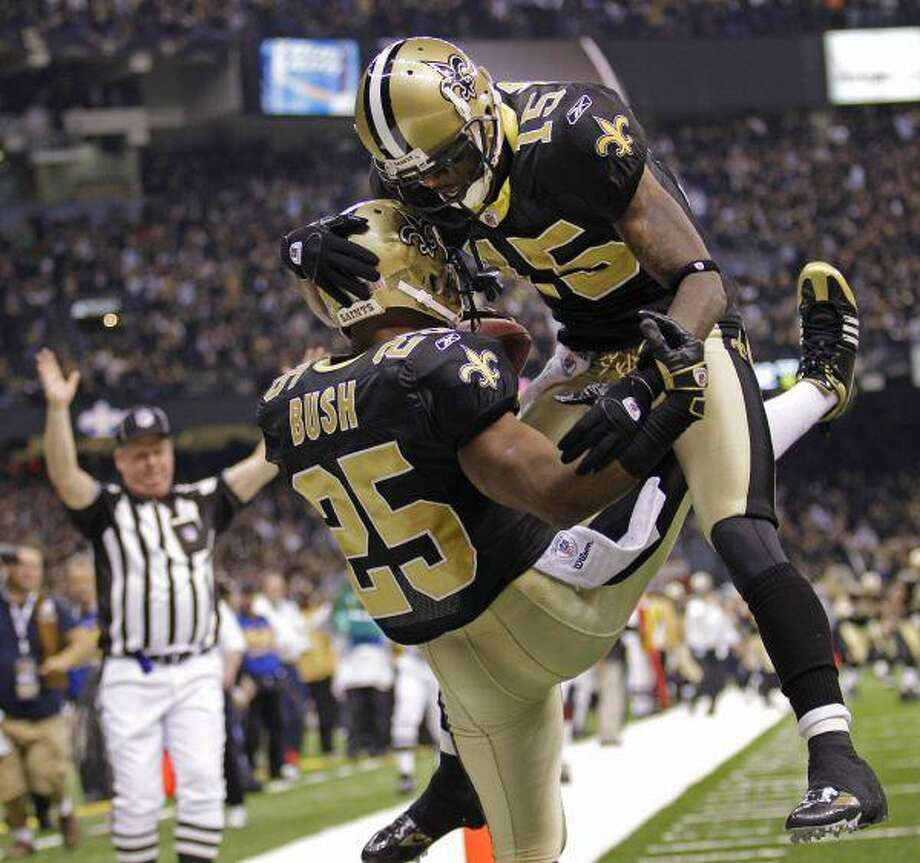 The Saints' Courtney Roby celebrates with running back Reggie Bush after Bush scored on an 83-yard punt return during the third quarter in New Orleans Saturday. / AP2010
