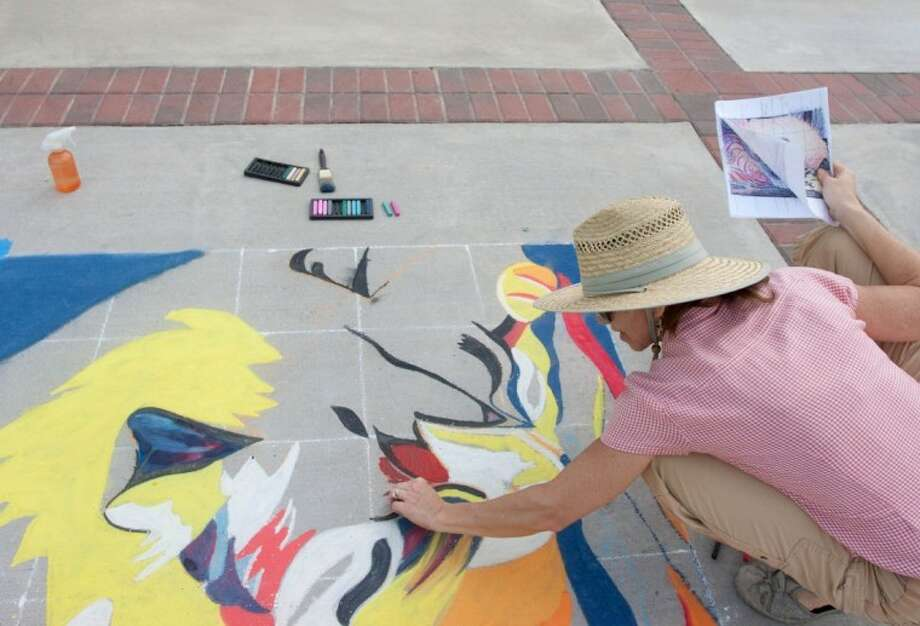 Artist Pat Vanvelzer works on a chalk mural at Conroe Founders Plaza during the second annual Chalk Up Conroe on Saturday. Fifteen local artists helped transform the plaza into a colorful collage of artwork. Photo: Staff Photo By Eric S. Swist