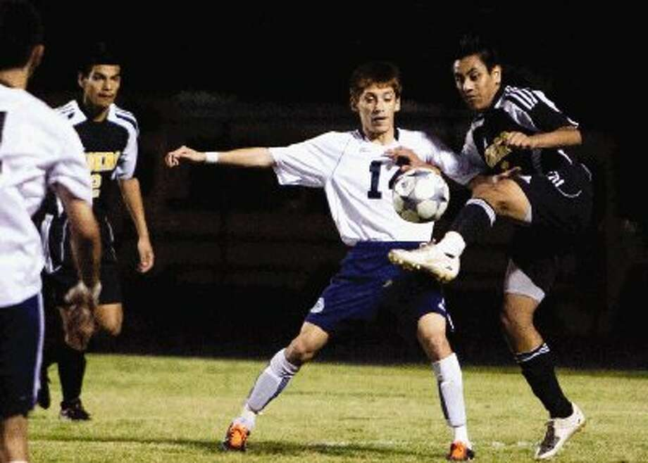 Conroe's Erick Coronilla battles for possession with College Park's Joel Botello during Friday night's district game. Photo: Staff Photo By Eric S. Swist
