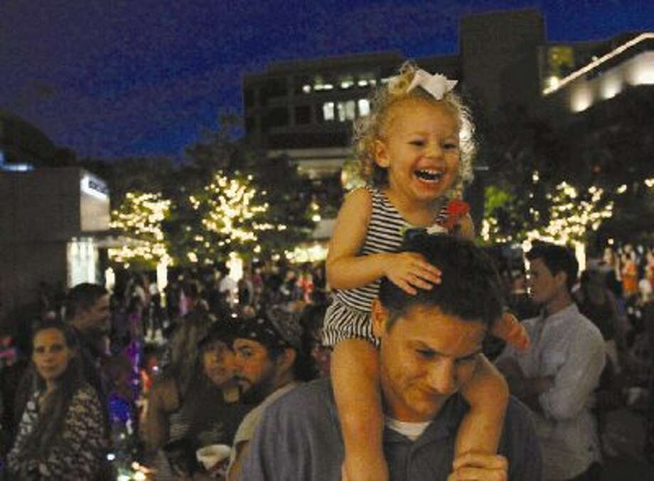 Kimley Cole, 2, laughs as music is played while her dad, Justin, holds her up so she can see the band during a Memorial Day celebration at The Woodlands Waterway on Sunday. Go to HCNPics.com to view and purchase this photo, and others like it. / Conroe Courier