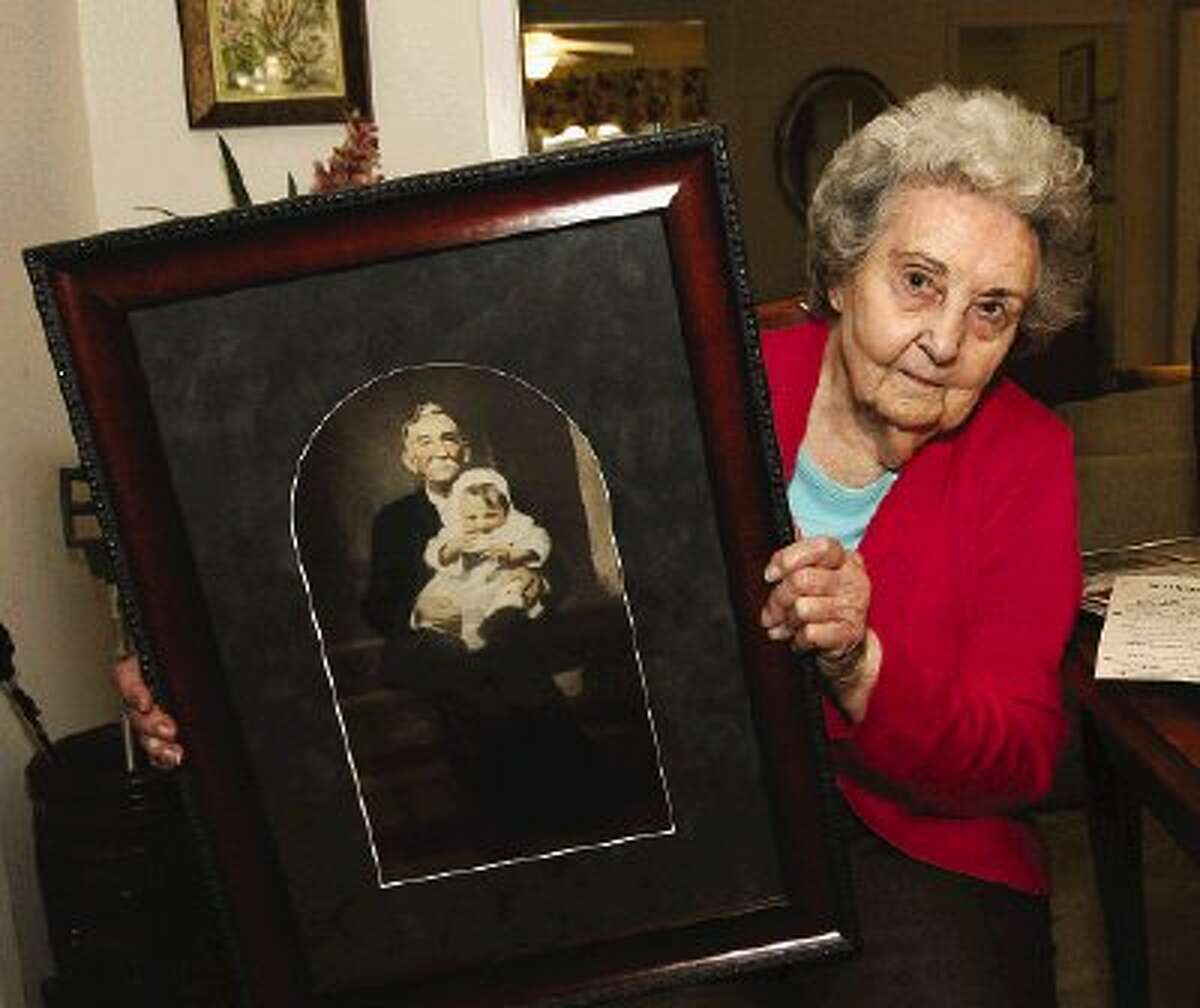 Floye Goodspeed displays a photo of herself sitting on the lap of her father, who was 75 when she was born.