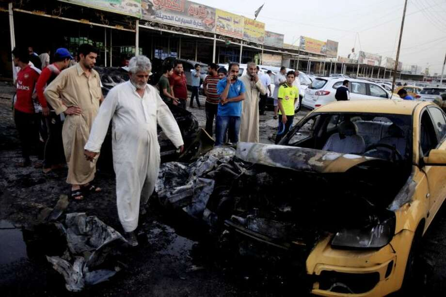 Iraqis gather at the scene of a car bomb attack at a used cars dealers parking lot in Habibiya neighborhood of eastern Baghdad, Iraq, Monday, May 27, 2013. A wave of car bombings tore through mostly Shiite Muslim neighborhoods of the Baghdad area, killing and wounding dozens of people, police said, in the latest outburst of an unusually intense wave of bloodshed roiling Iraq. The blasts are the latest indication that Iraq's security is rapidly deteriorating. Photo: Karim Kadim