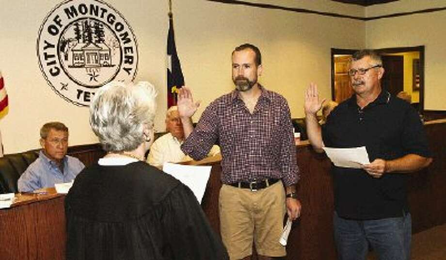 Montgomery Municipal Judge Margaret Robbins administers the oath of office to Position 5 Councilman Dave McCorquodale, left, and returning Position 3 Councilman Kirk Jones at Tuesday's City Council meeting.