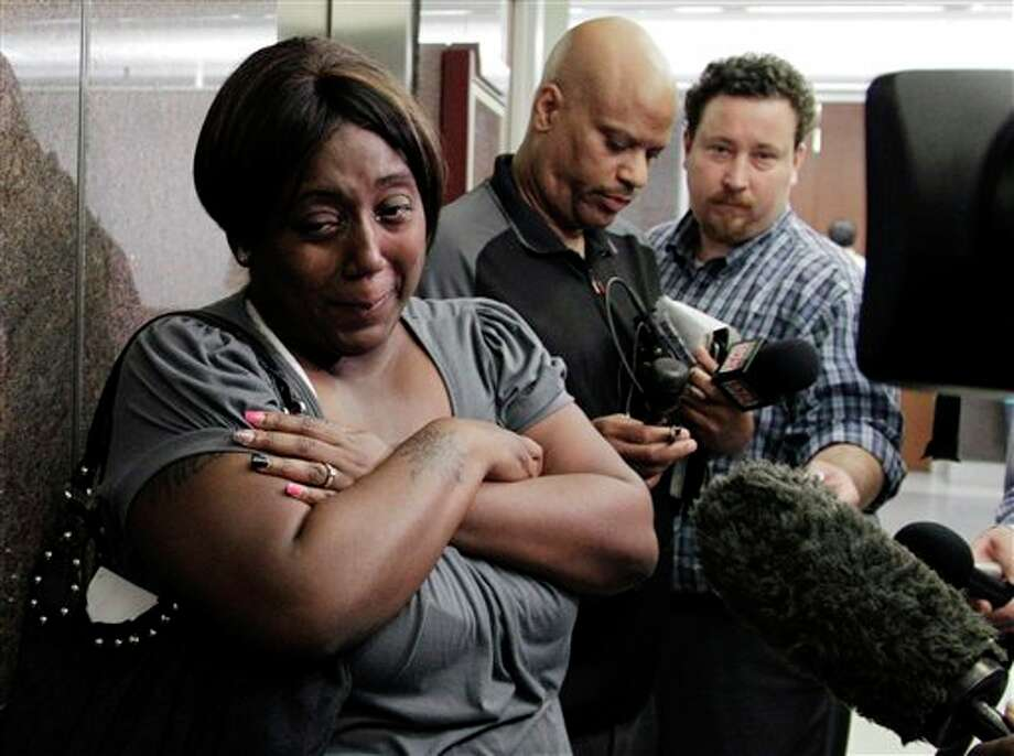 Auboni Champion-Morin, left, turns away from reporters after a status hearing in juvenile court Thursday, March 15, 2012, in Houston. Champion-Morin's son vanished eight years and was recently found. The former babysitter, 26-year-old Krystle Rochelle Tanner, was arrested Monday on a kidnapping charge. She was being held in jail in San Augustine, a community about 140 miles northeast of Houston. (AP Photo/Pat Sullivan) Photo: AP Photo By Pat Sullivan / AP