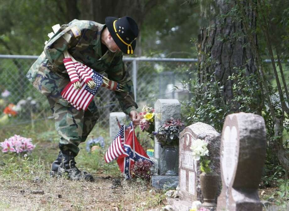 David Allen, a retired U.S. Army first sergeant from the Gulf War, places flags on grave markers of veterans following the Memorial Day ceremony Monday at the C.M. Joslin American Legion Post in Willis. Photo: Staff Photo By Eric Swist