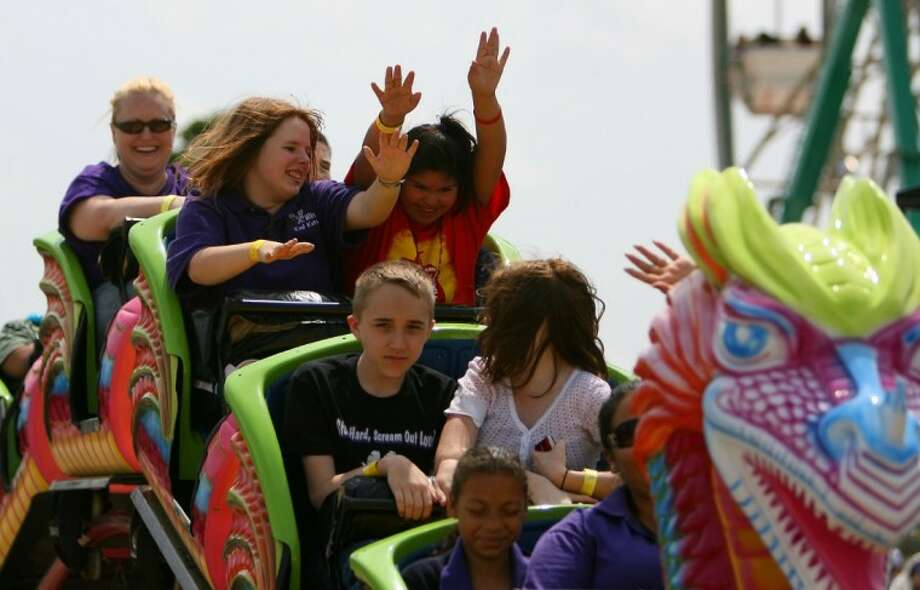 Lynn Lucas Middle School students Amber Hutchinson, left, and Maria Nuna, enjoy a ride on a roller coaster during Special Education Day Friday at the Montgomery County Fair and Rodeo.