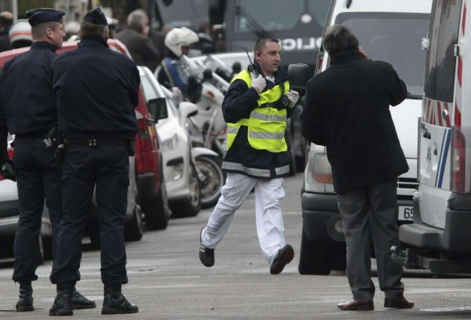 A French doctor runs to assist the injured after an Islamic extremist died after jumping from his window, gun in hand, in a fierce shootout with police in Toulouse, France Thursday. Photo: Bob Edme