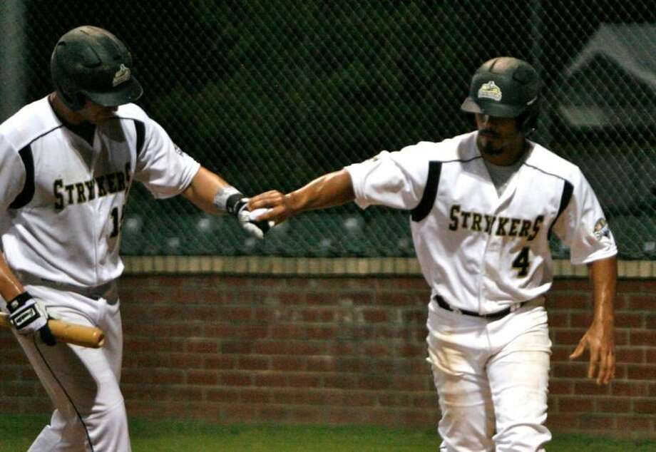 The Woodlands Strykers' Kevin Santana, right, celebrates a run with teammate Brian Smith during Wednesday night's doubleheader against The Texas Marshals. The Strykers lost Game 1, dropping a 6-3 decision. Photo: Staff Photo By Eric Swist