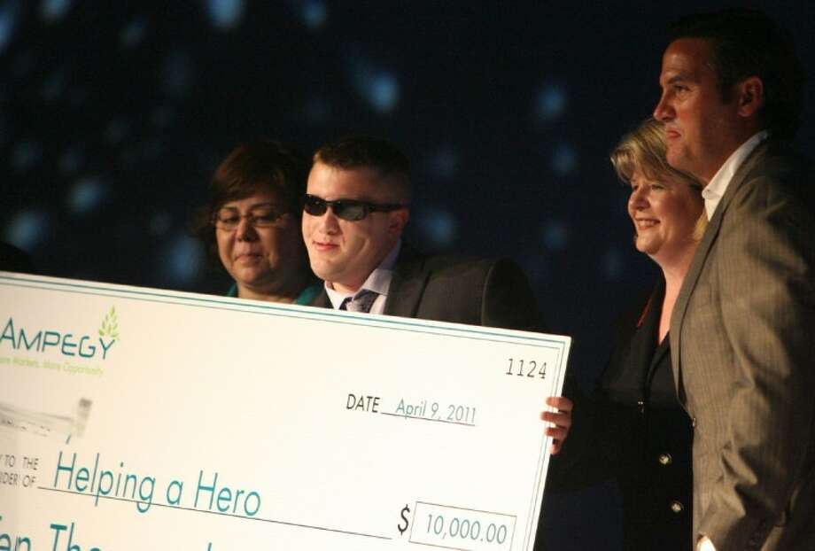 U.S. Army Pfc. Hunter Levine (Ret.) holds up a check for $10,000 given to him by Ampegy during a surprise announcement Saturday to aid in the construction of a custom home for Levine, who is blind after being injured in the Iraq war, through the Helping a Hero project.