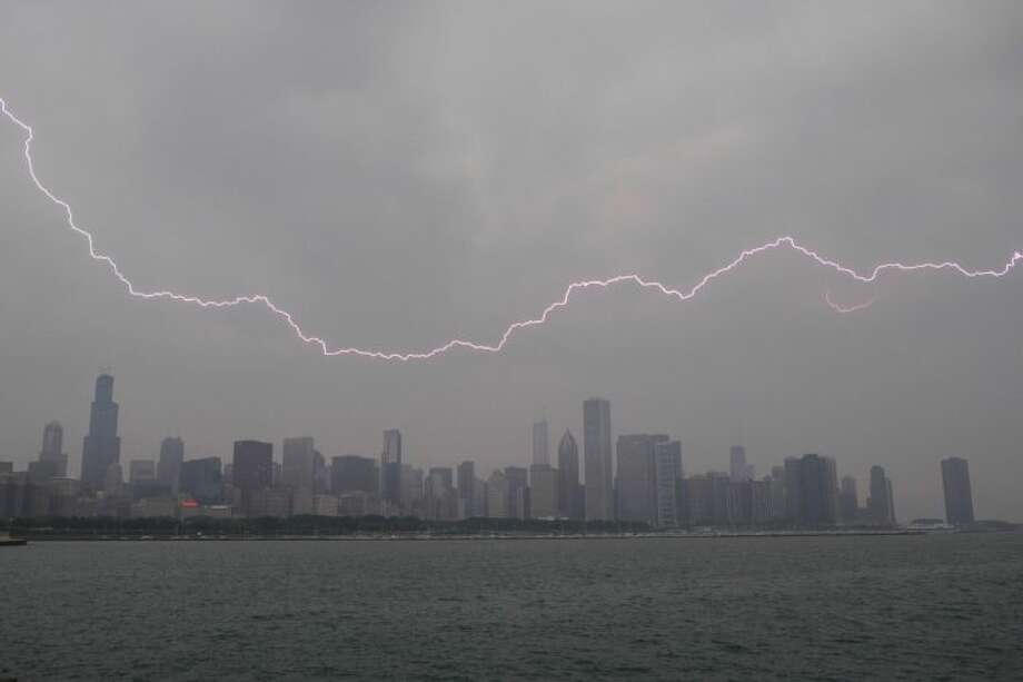 Lighting flashes over the Chicago skyline, Wednesday, June 12, 2013. An unusually massive line of storms packing hail, lightning and tree-toppling winds was rolling through the Midwest on Wednesday and could affect more than one in five Americans from Iowa to Maryland. Photo: Scott Eisen