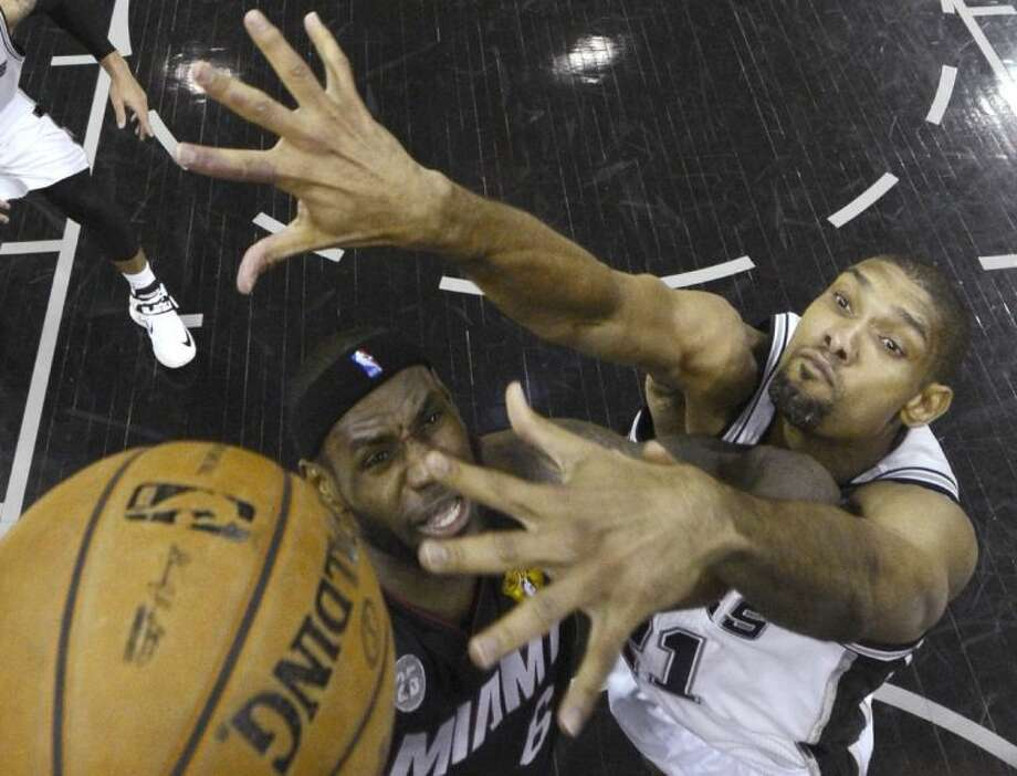 The Miami Heat's LeBron James, left, tries to shoot against San Antonio Spurs' Tim Duncan in Game 4 of the NBA Finals. The Spurs won 109-93 to even the series at two games each. Photo: Derick E. Hingle