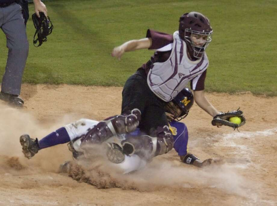 Montgomery's Karissa Allen is out at home plate after sliding under Magnolia's Emily Garza Friday at Montgomery High School. See more photos online at yourhoustonnews.mycapture.com. Photo: Karl Anderson