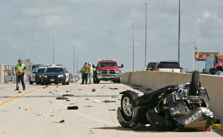 An overturned motorcycle is seen as Conroe Police officers examine the scene of a fatal wreck Thursday morning on the southbound lanes of Interstate 45 in Conroe. Photo: Staff Photo By Eric Swist