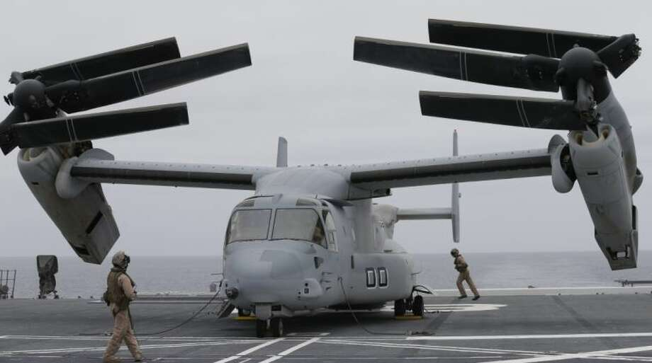 Marines secure an MV-22 Osprey aircraft as it folds to be lowered into the hanger aboard the Japanese destroyer JS Hyuga in coastal waters off San Diego Friday in San Diego. Photo: Gregory Bull