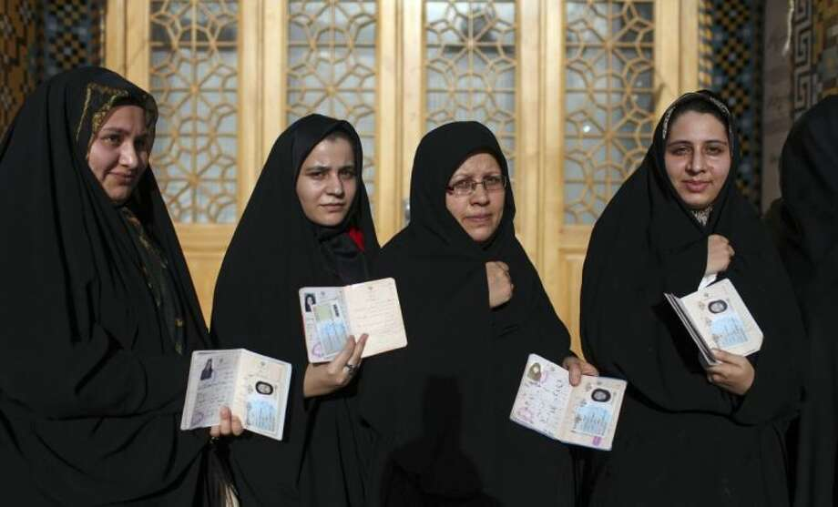 Iranian women display their identification cards as they line up to vote in the presidential and municipal council elections at a polling station in Qom, 78 miles south of the capital Tehran, Iran, Friday. Photo: Ebrahim Noroozi
