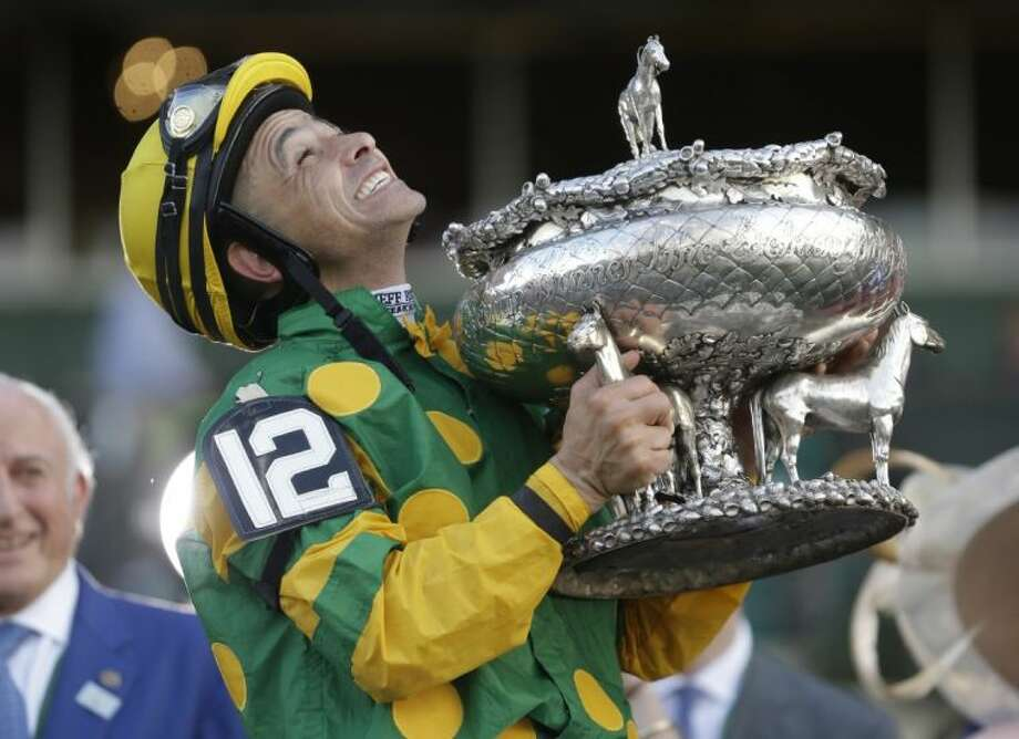 Jockey Mike Smith holds the Belmont Stakes trophy in the winner's circle after riding Palace Malice to win the race. Photo: Seth Wenig