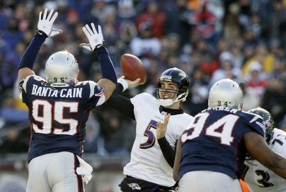 Baltimore Ravens quarterback Joe Flacco looks to pass under pressure from New England Patriots linebacker Tully Banta-Cain and Ty Warren during the first quarter in Foxborough, Mass., Sunday. / AP2010