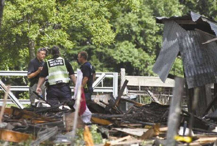 Officials examine the scene of a home explosion Tuesday, June 11, 2013 in Dobbin, Texas. Two adults and a child were transported from the home by medical helicopter. The cause of the explosion is still under investigation. The Montgomery County Fire Marshal's Office confirmed Thursday that Jennifer Mock has died after being injured when the home she was in exploded Tuesday morning. Photo: Catherine Dominguez / AP