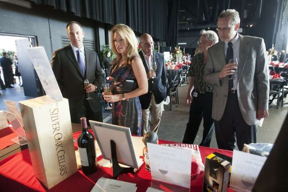 Guests browse the silent auction table at The Cynthia Woods Mitchell Pavilion Partners Wine Dinner and Auction on Sunday. The 14th annual event raised more than $129,000 for scholarships and The Pavilion's educational outreach programs. Photo: Karl Anderson